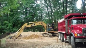 A backhoe breaking ground on a new home